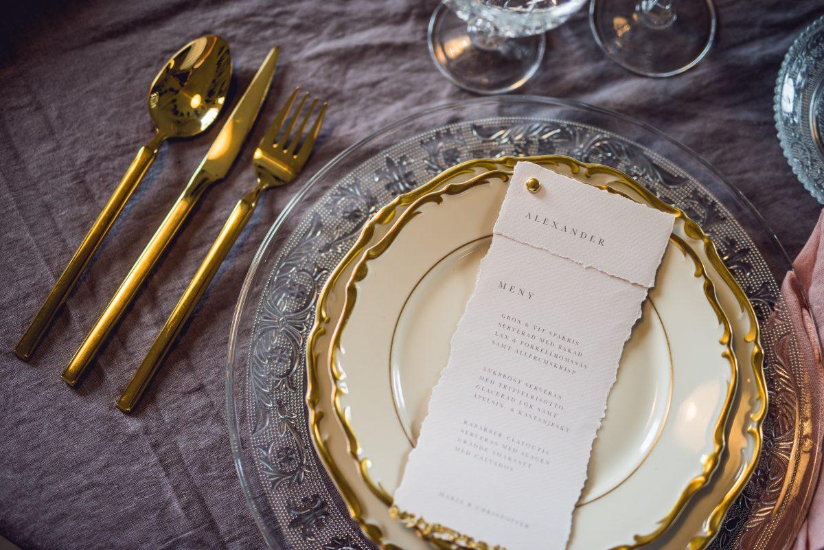 Tallrikar med guldkant, guldbestick och kristallglas